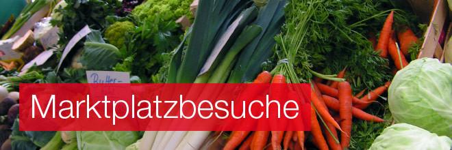 Die Auslage eines Gemüsehändlers mit verschiedenen Gemüsesorten, Aufschrift: Marktplatzbesuche