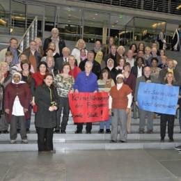 Gruppenfoto: Die Besuchergruppe aus Hannover zeigt Plakate mit den Forderungen der Hannoverschen Initiative für Soziale Stadt (HISS)