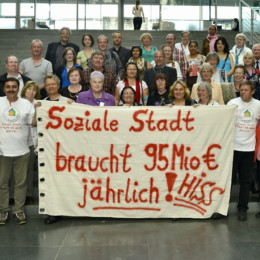 """Gruppenfoto der Besuchergruppe mit Kerstin Tack: Die Gruppe hält ein Transparent; """"Soziale Stadt braucht 95 Millionen Euro jährlich!"""""""