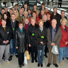 Gruppenfoto der großen Besuchergruppe in der Kuppel des Reichstagsgebäudes