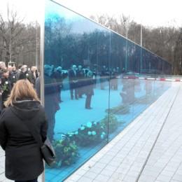 Eine blaue Plexiglas-Wand, an der Kränze zum Gedenken niedergelegt worden sind