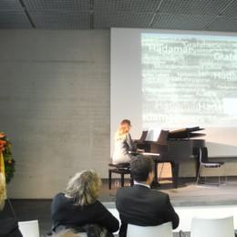 Junge Musikerin am Flügel auf dem Podium