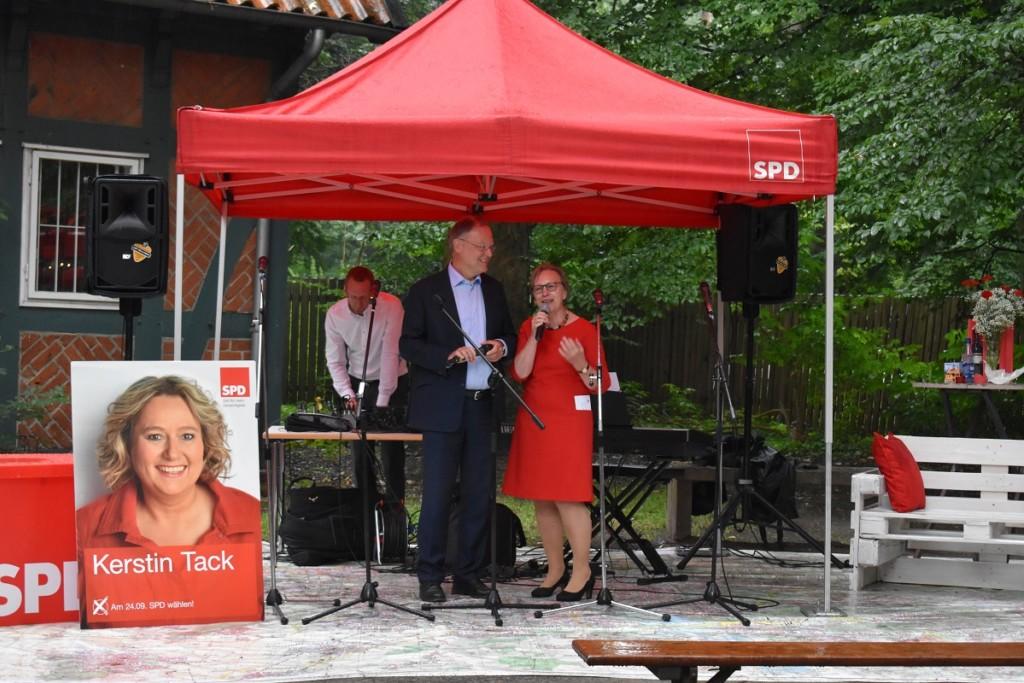 Stephan Weil und Gabriele Lösekrug-Möller unter dem Pavillon beim Auftackt, im Vordergrund ein Plakat mit Kerstin Tack, im Hintergrund Helge Adam, Keyboarder der Mig-Pop-Kids