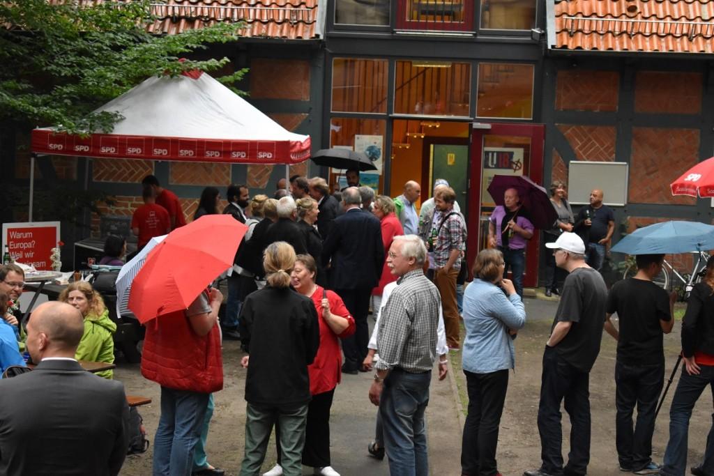 Die Gäste unterhalten sich in lockerer Atmosphäre im Innenhof des Falkenjugendzentrums. Im Hintergrund ist der Getränkeausschank zu sehen, der vom Jungen Team Kerstin Tack betreut wird.